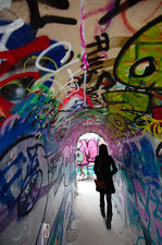 Pedestrian in graffiti-covered tunnel