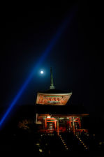 Blue light beam and moon over red pagoda in Kiyomizudera