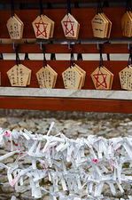 Ema votive offerings and tied umikuji fortunes in Shinyo-do temple